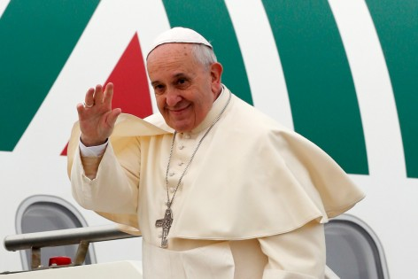 Pope Francis waves as he boards a plane at Fiumicino Airport in Rome